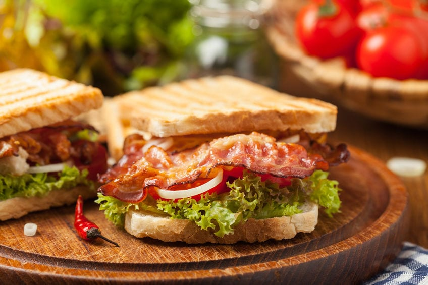 Toasted sandwich with bacon, tomato, cucumber and lettuce
