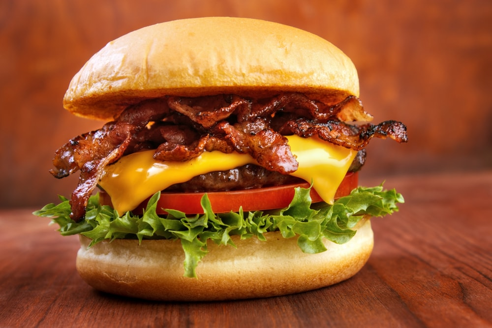Burger with lettuce, bacon, cheese, and tomato