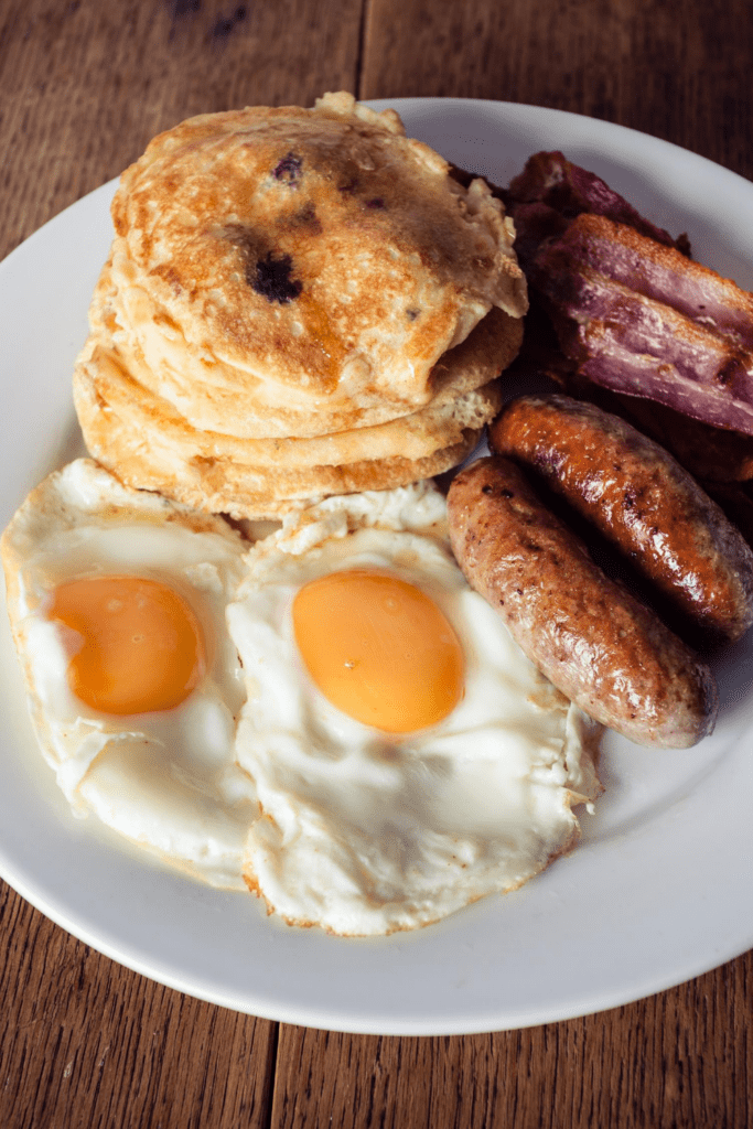 Pancakes with Fried Eggs, Bacon and Sausage for Breakfast