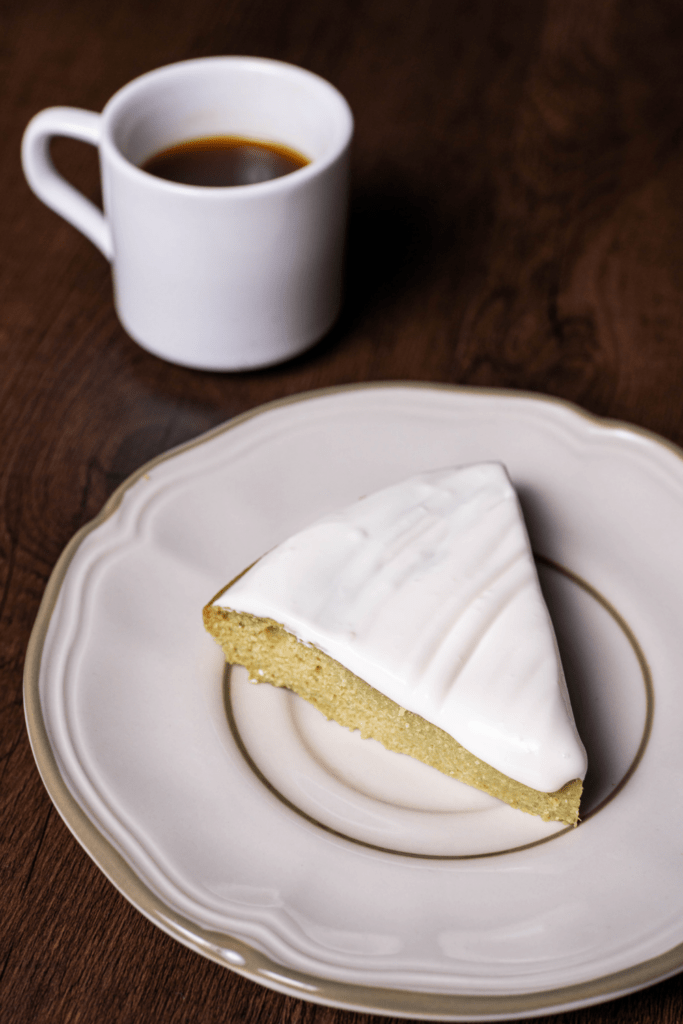 A slice of key lime cake with a cup of coffee