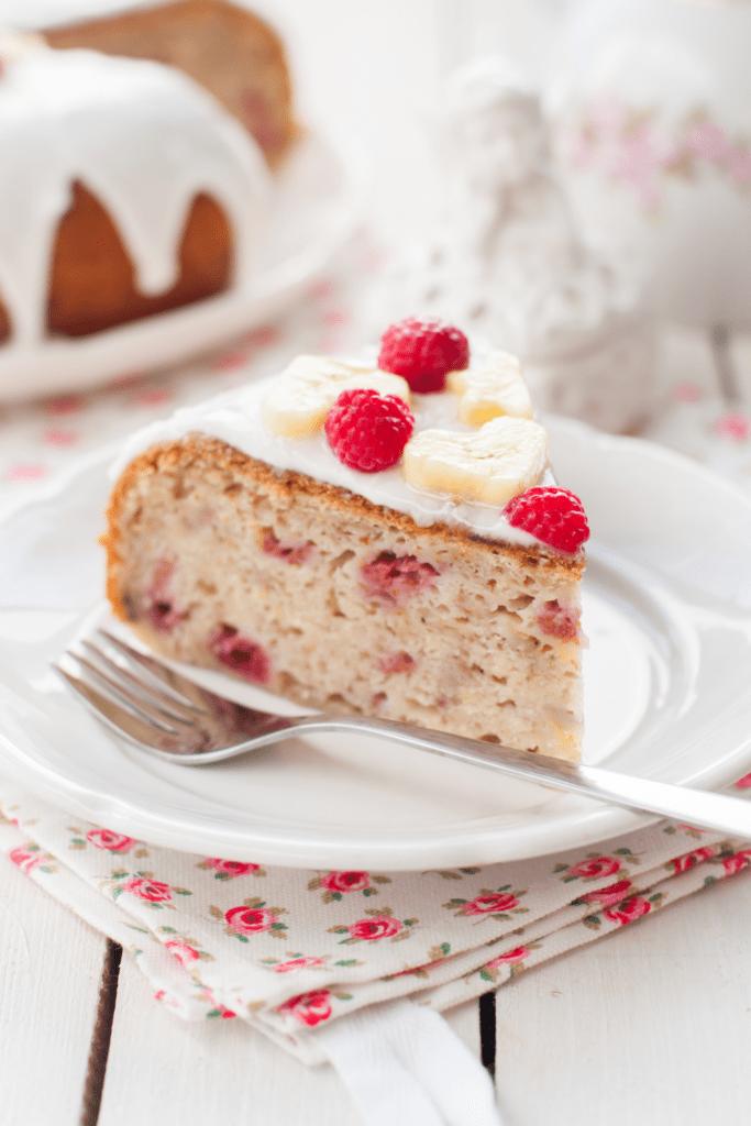 Slice of Banana Cake with Sugar Glaze, Raspberries and Banana Slices Toppings
