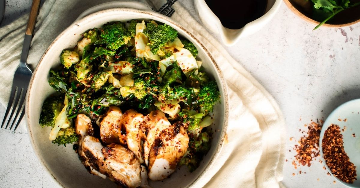 A Bowl of Stir-Fried Green Vegetables with Grilled Chicken and Garlic