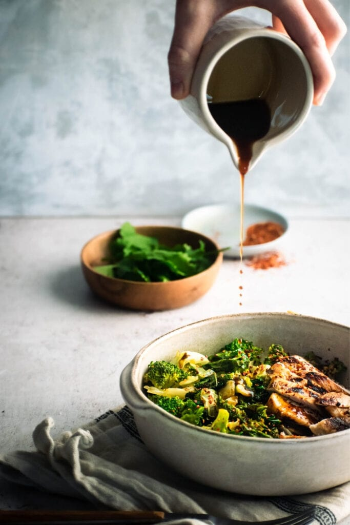 Pouring Soy Sauce into a Bowl of Green Vegetables and Grilled Chicken