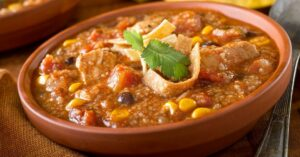 A Bowl of Chicken Tortilla Soup with Corn, Black Beans and Tomatoes