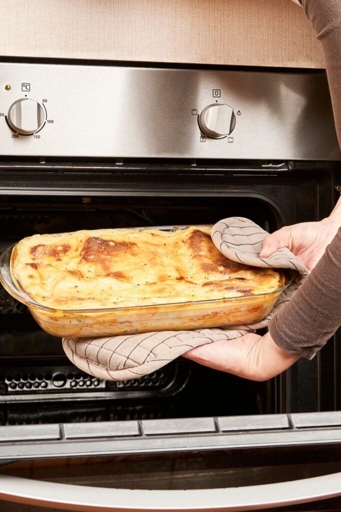Woman Holding a Lasagna in the Oven