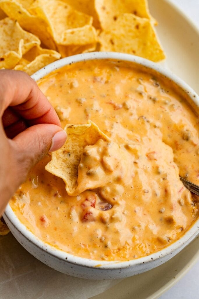 Dipping Tortilla Chips on a Cheesy Sausage Dip
