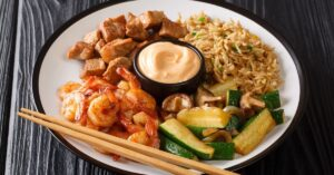 Hibachi Dish: Fried Rice, Zucchini, Shrimp, and Steak Served with Sauce in a Plate