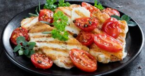 Homemade Grilled Halloumi Cheese with Tomatoes on a Black Plate