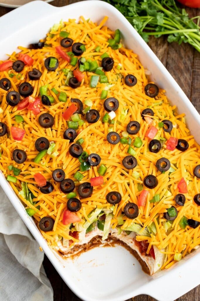 Cheesy Seven-Layer Taco Dip with Onions, Tomatoes and Black Olives