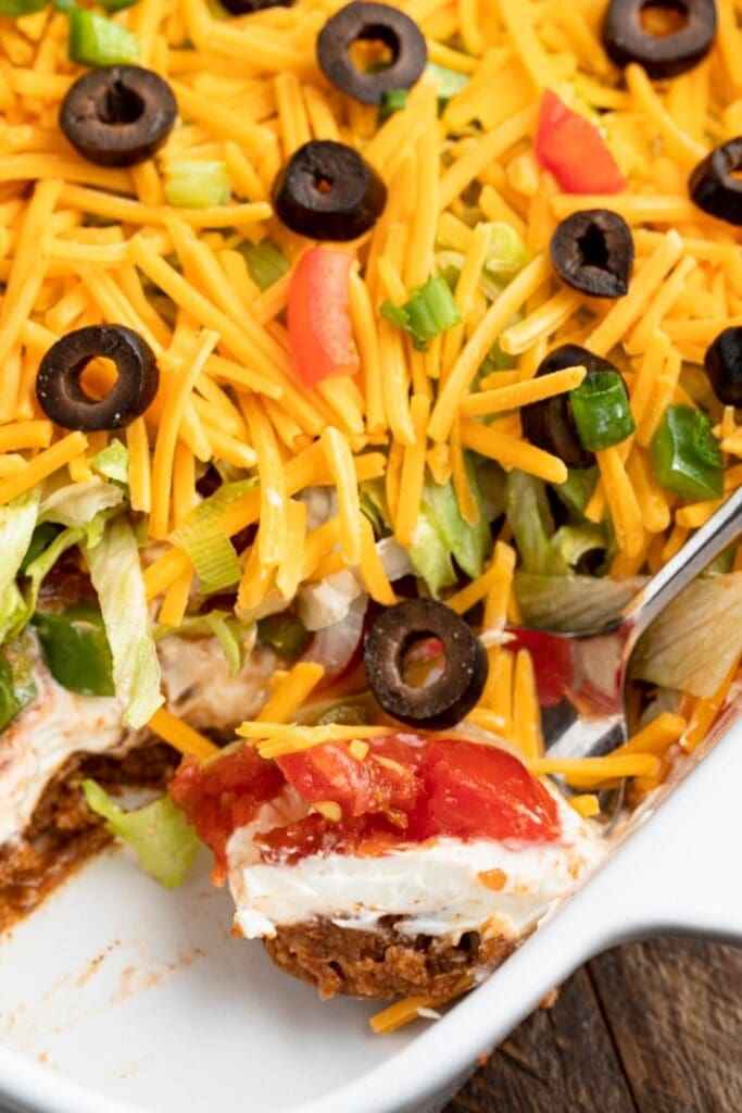 Homemade Cheesy Seven Layer Taco Dip with Black Olives, Tomatoes and Onions