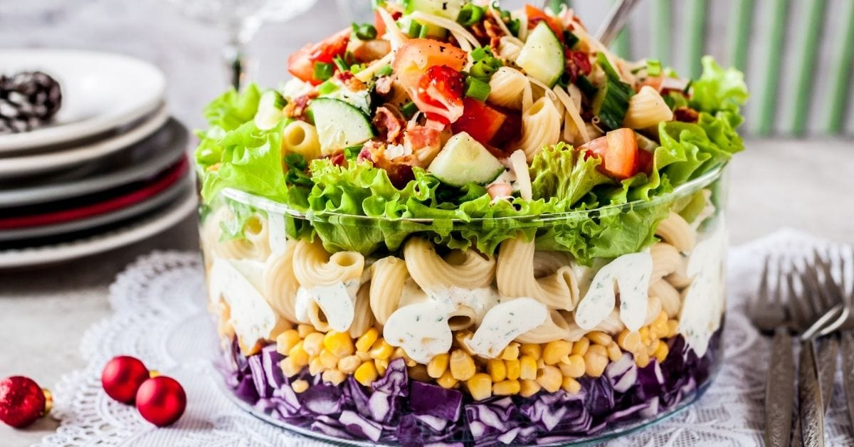 A Bowl of Layered Pasta Salad with Red Cabbage, Corn, Tomatoes, Cucumber and Herbs
